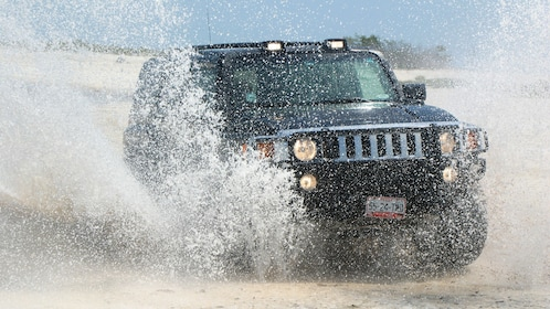 Hummer driving in to the waters in Cancun