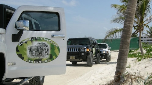 Three hummer cars parked alongside the beach in Cancun