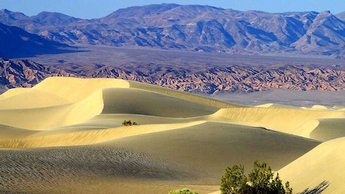 Scenic view of Death Valley with sand dunes in the forefront and mountains in the distance