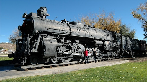 Tourists look closely upon a classic steam locomotive