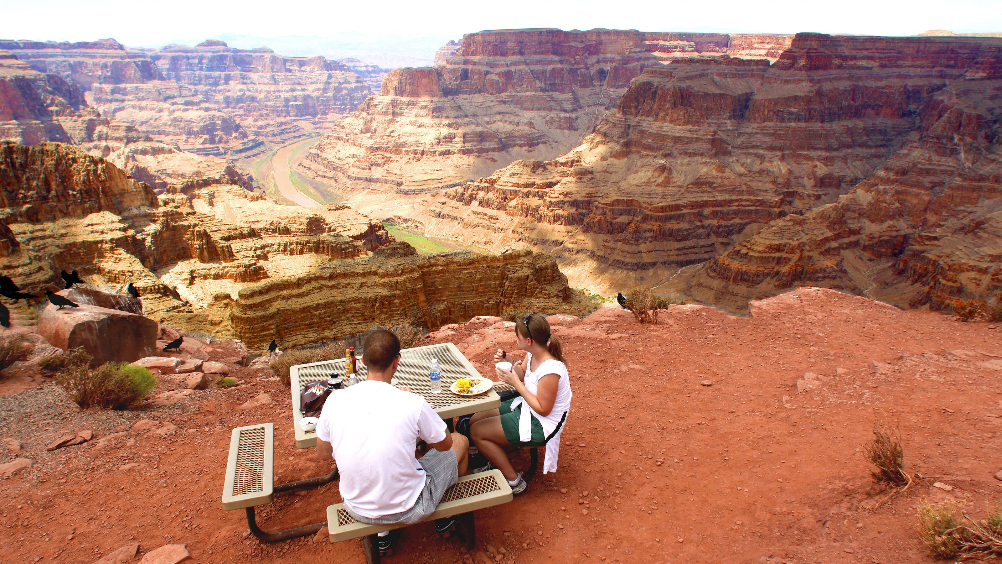 Couple enjoying a delicious meal atop the Grand Canyon with panoramic views