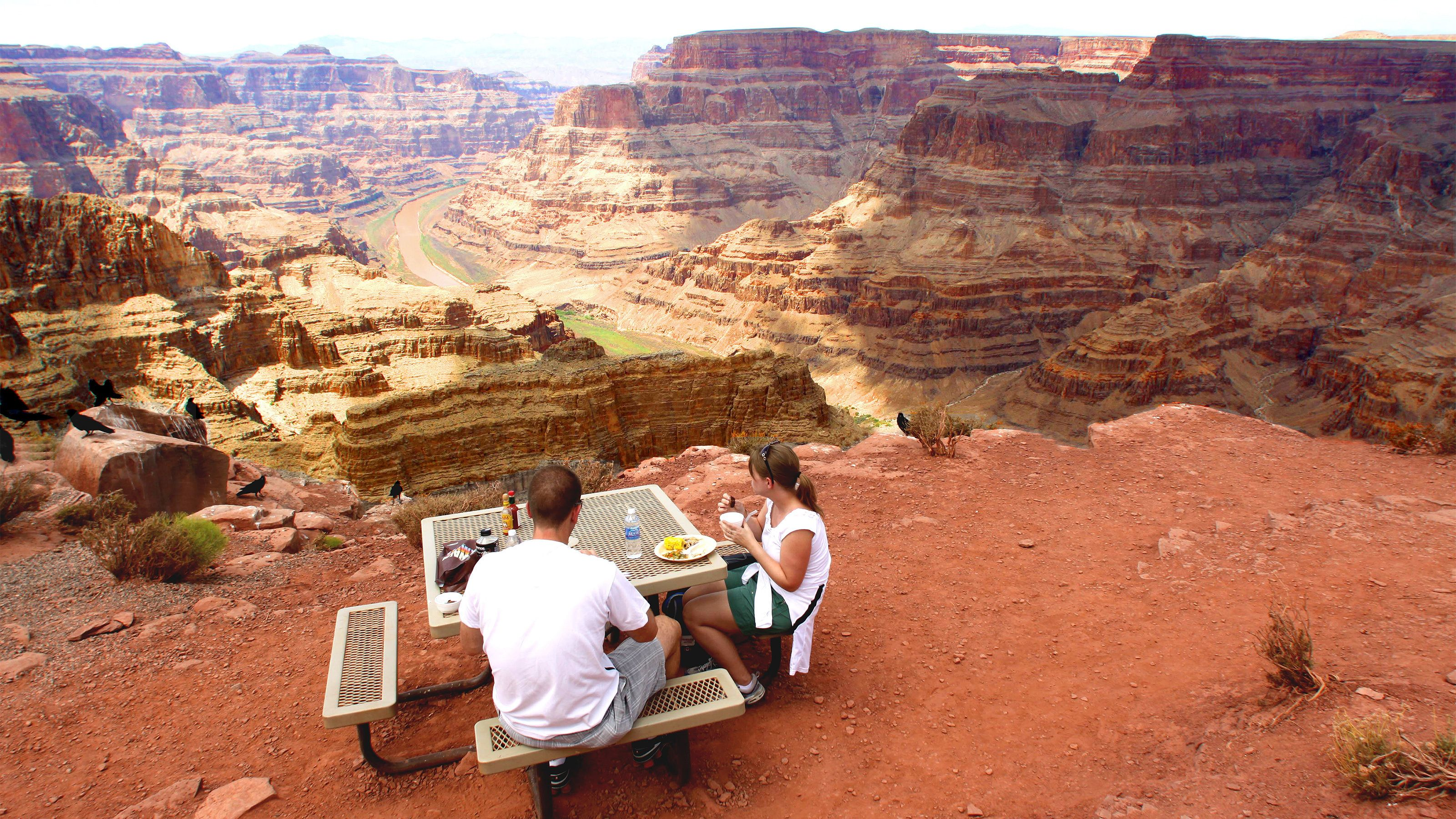 Couple enjoying a delicious lunch atop the Grand Canyon with panoramic views