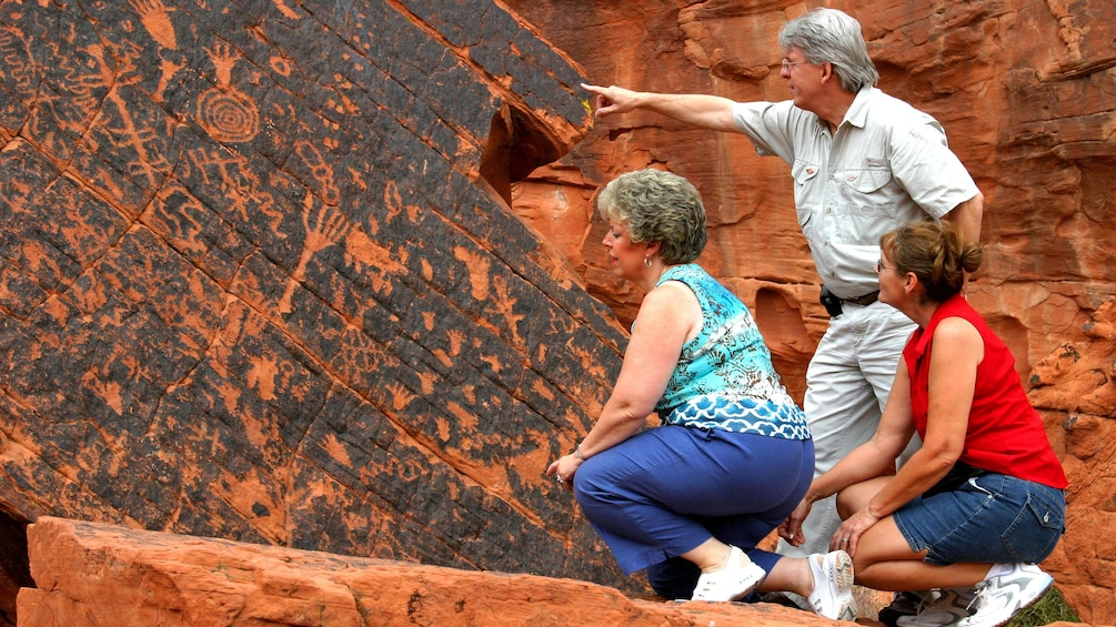 Show item 5 of 5. Tourists inspect ancient cave drawings