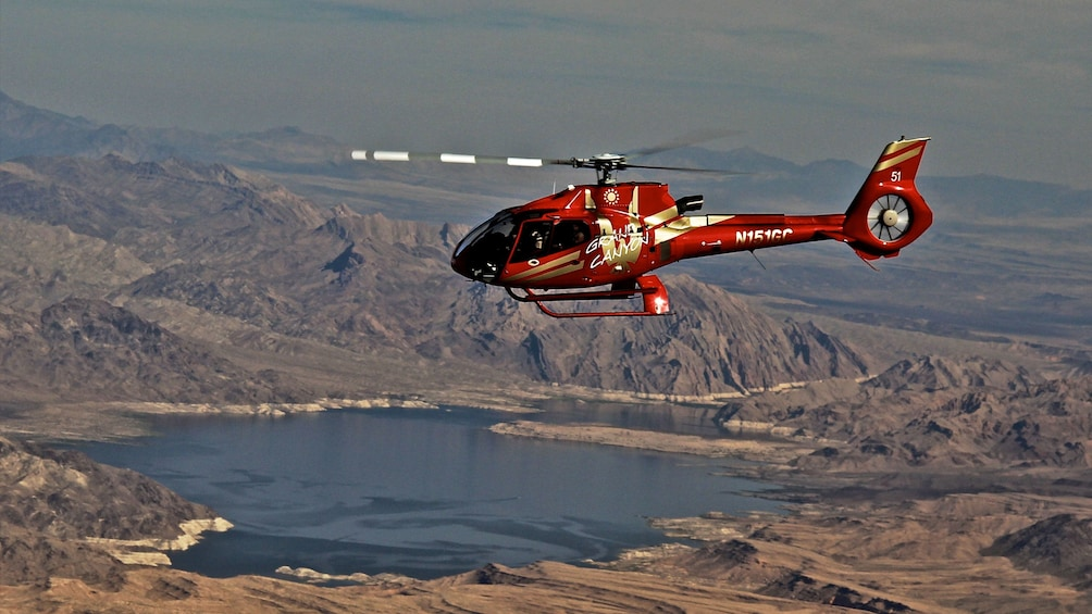 Show item 1 of 8. Aerial view of the Grand Canyon with a helicopter on tour in Arizona