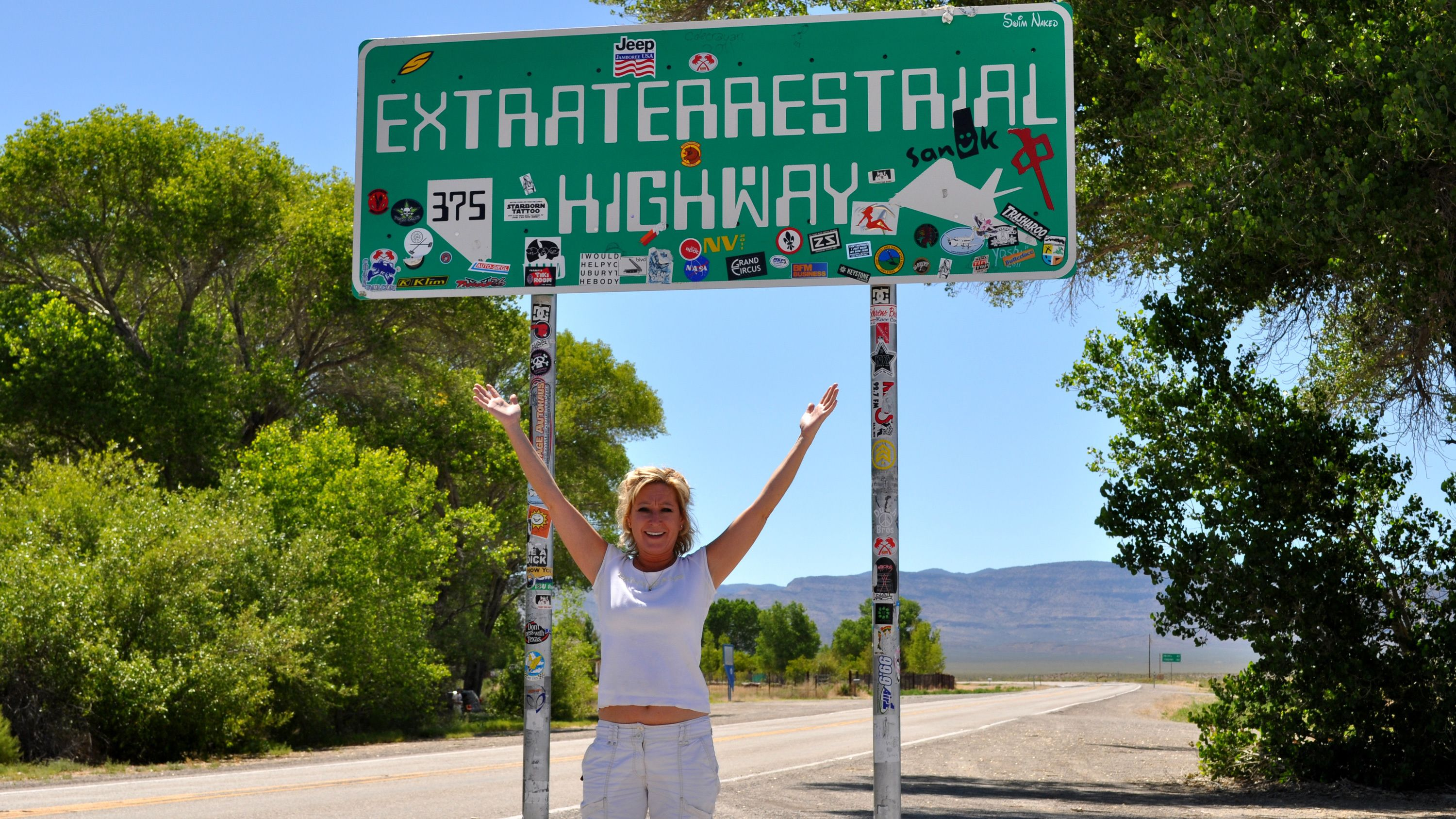 Adventurous woman taking a photo along the Extraterrestrial Highway at midday