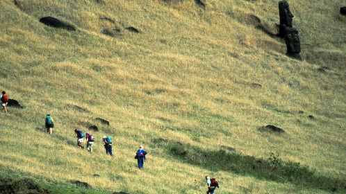 People hiking past statues on Easter Island