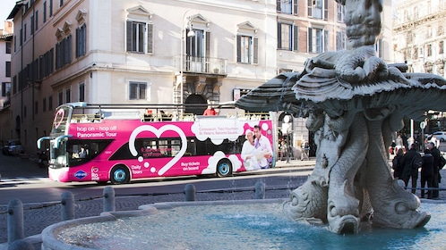 Landscape photo of an Trevi fountain with the tourbus in the background.