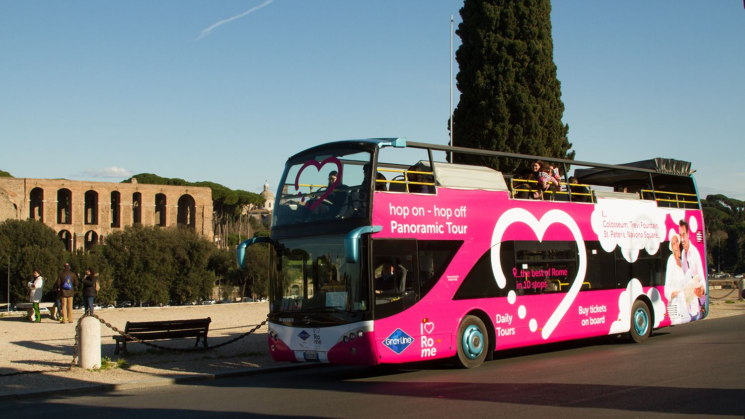 Photo of the tourbus parked outside an ancient roman forum.