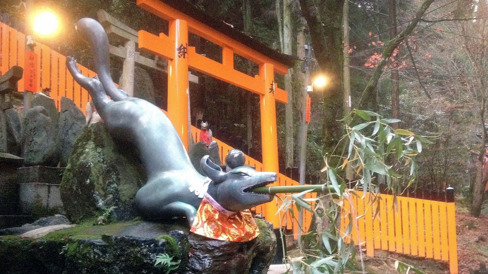 正在顯示第 4 張相片,共 5 張。 A Foz sculpture sits beside a torii gate at the entrance to Fushimi Inari shrine in Kyoto