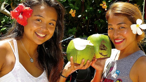 Two young ladies holding their freshly cut coconuts in Saipan on a sunny day
