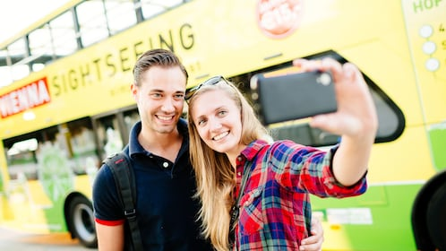 Couple taking a selfie in front of sightseeing bus in Vienna
