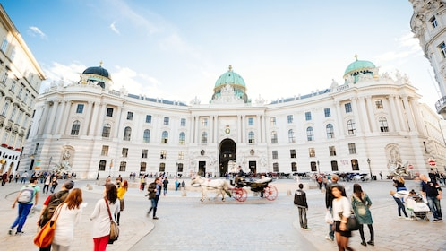 People walking through courtyard outside Hofburg Palace in Vienna