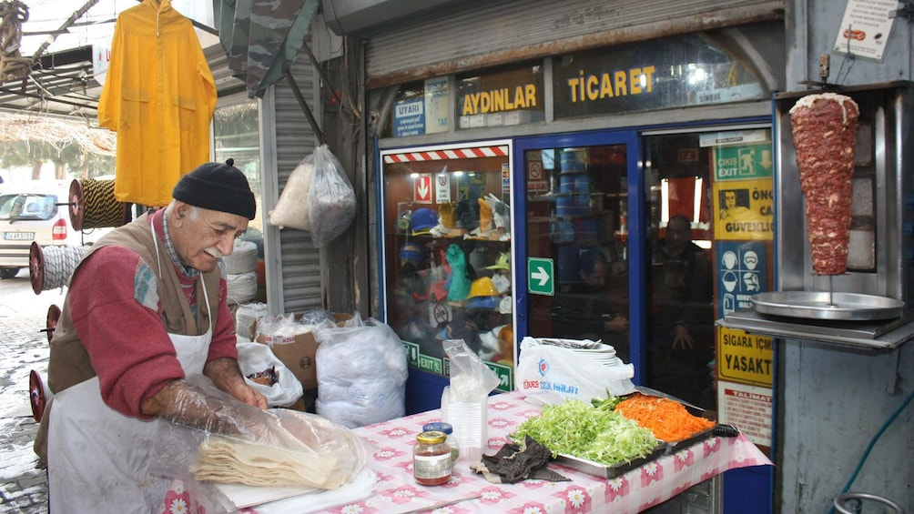 Foto 4 von 5 laden Man standing and preparing food at a food stall in Istanbul