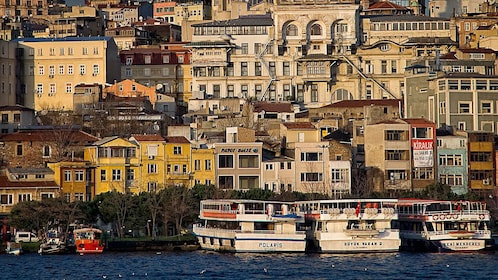 Boats on the water with houses and buildings in the background in Turkey
