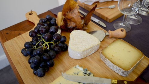Cheeses and grapes on a sampling board at the cheese and wine tasting in Cannes