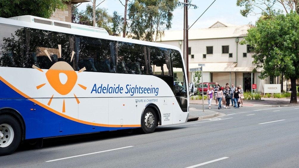 Show item 4 of 4. Traveling bus with people for the Adelaide City Highlights Tour.