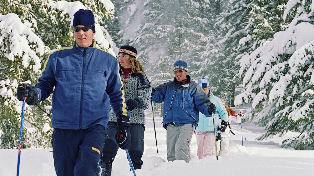 Cargar ítem 1 de 4. Group snowshoeing in knee deep snow in Denver