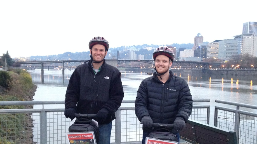 two guys riding segways on a lookout point near the river in downtown Portland