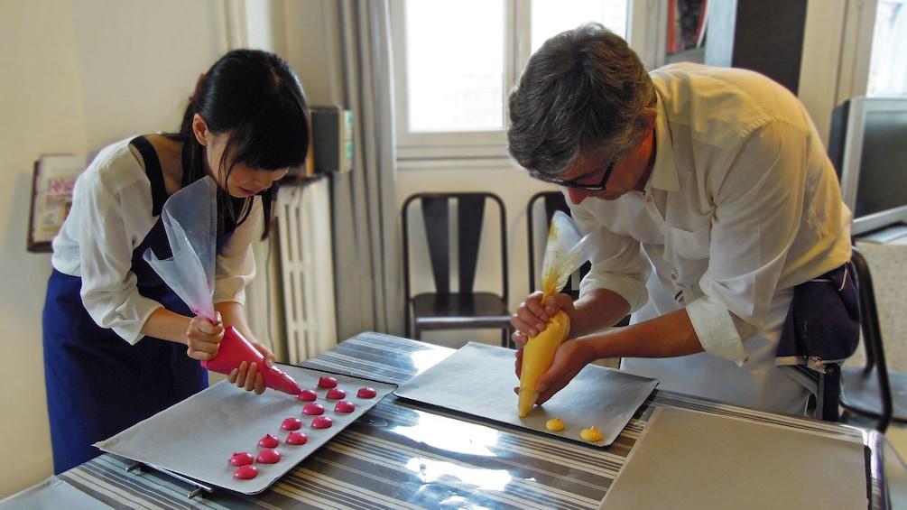 Foto 2 van 4. Piping macaroons onto a baking sheet