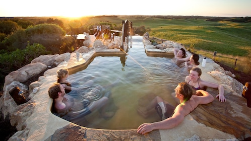 Group relaxes in stone hit springs pool at sunset