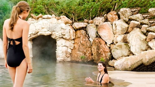 One woman sits in hot springs while another prepares to enter the water