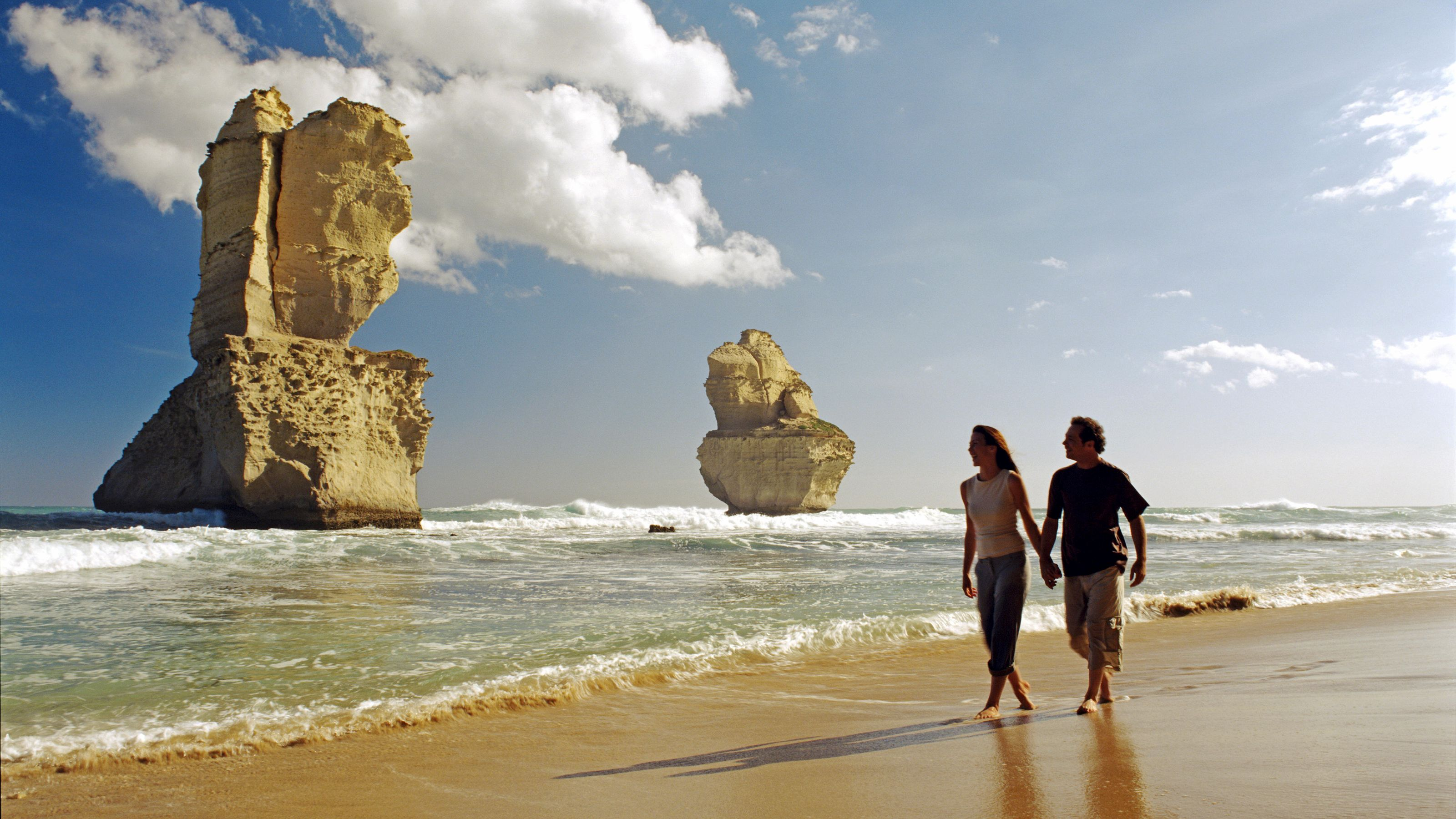 Couple stroll hand in hand along beach on the Great Ocean Road