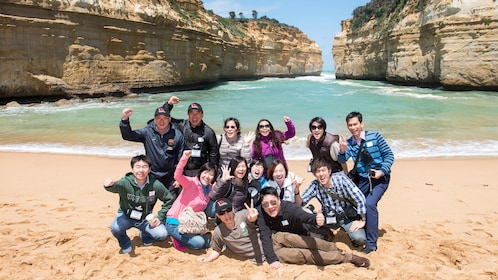 Group posing for camera on beach along the Great Ocean Road