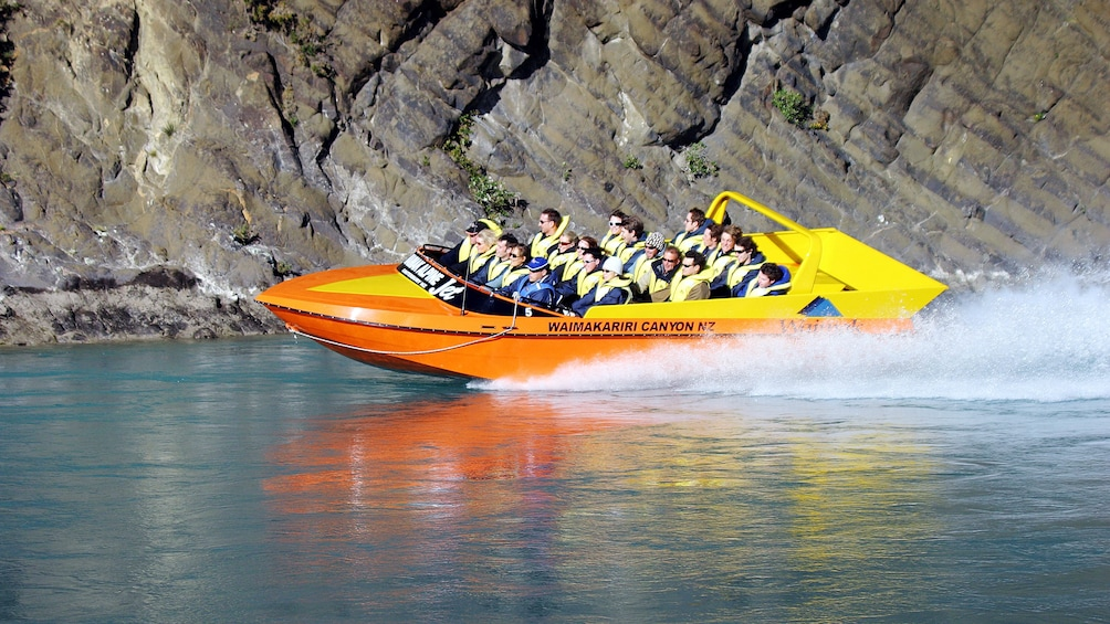 Show item 1 of 5. Jet boat in Waimak Gorge with riders next to cliffs in New Zealand.