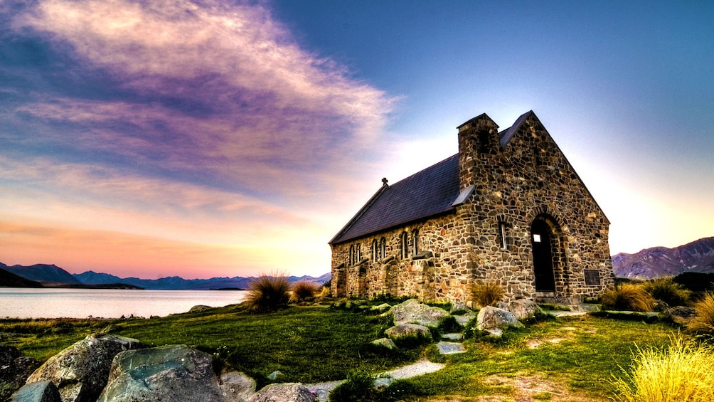 Show item 1 of 5. Stone building on shores of Mount Cook in New Zealand.