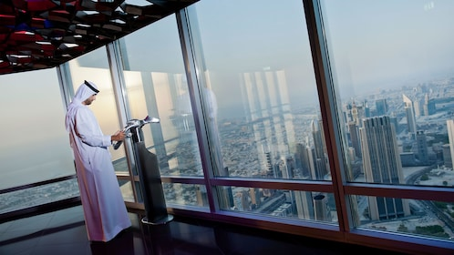Man looking out at the city of Dubai from the observation deck at Burj Khalifa