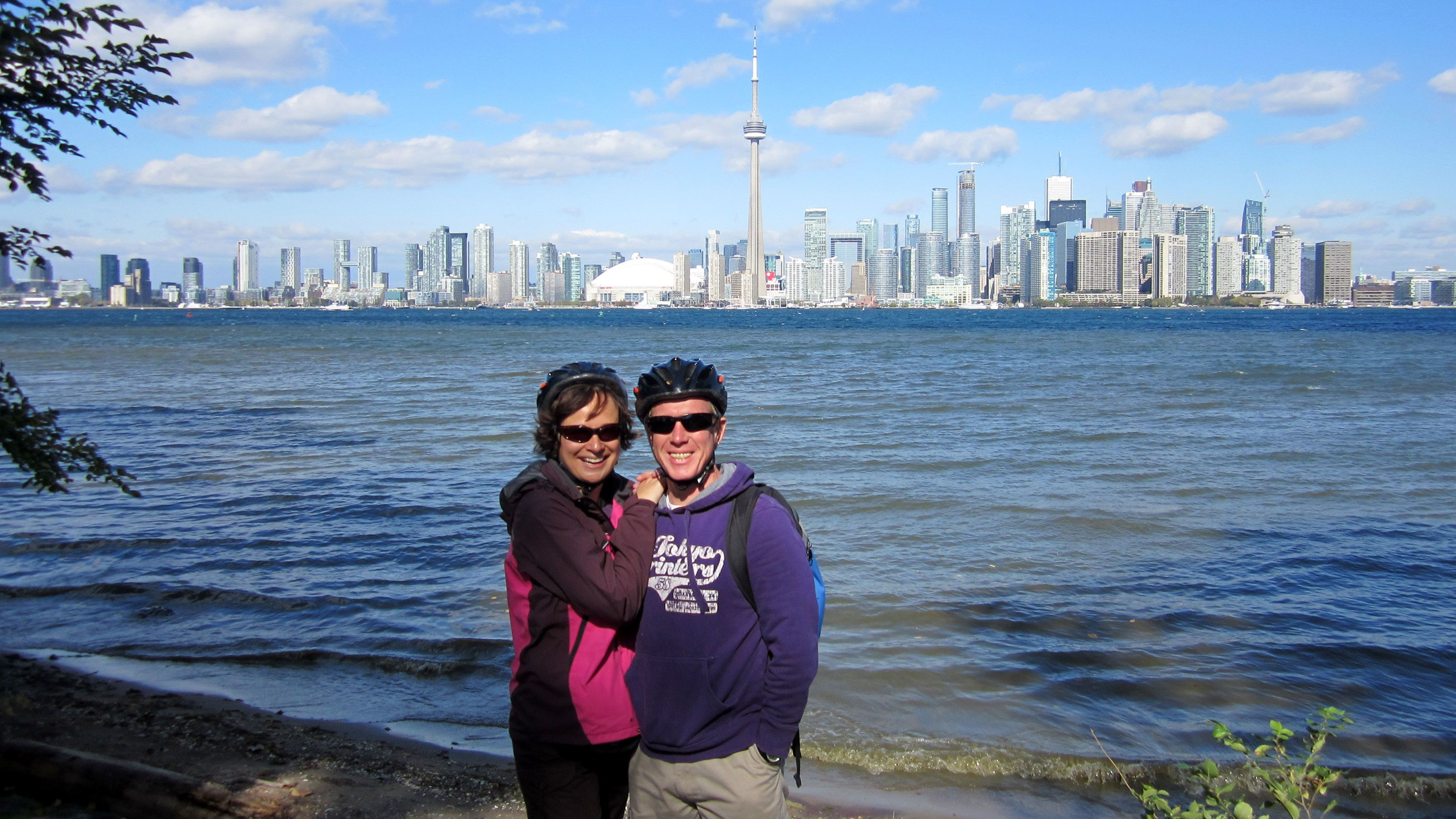 Two people pose for a photo in front of the Toronto skyline