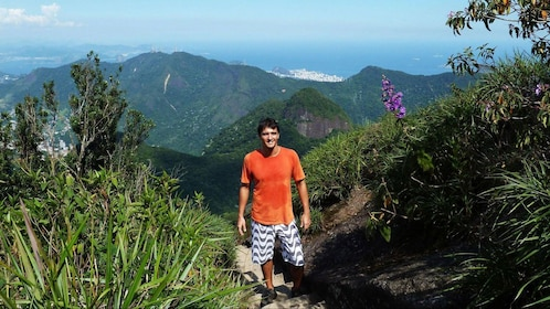 Hiking man on a trail in Pica da Tijuca in the rainforest of Rio de Janeiro