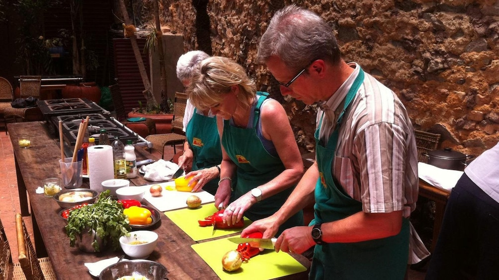 Show item 10 of 10. Cooking class chopping vegetables