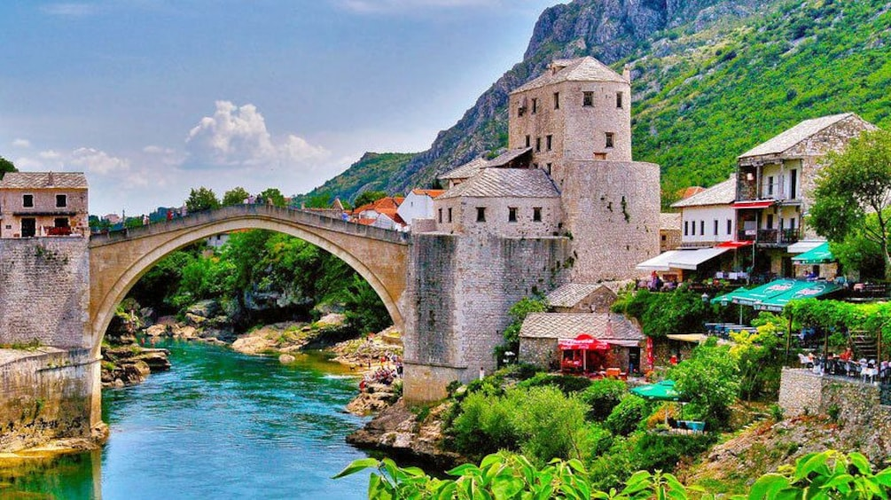 Show item 1 of 5. Crossing the old bridge of Stari Most in Mostar