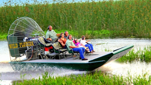 Small airboat speeds through the everglades with passengers in Orlando.