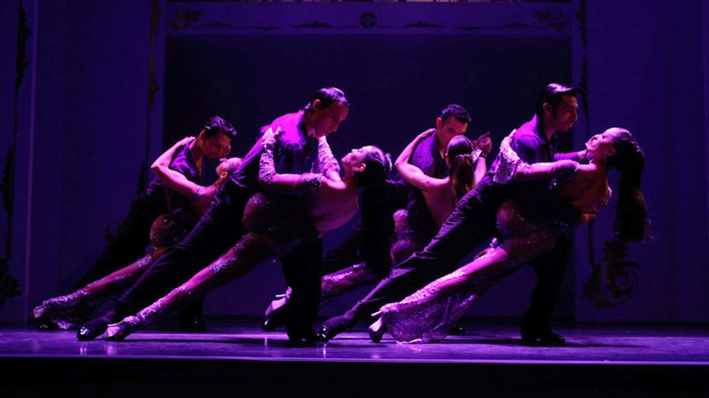 1 枚目の写真 (9 枚中) を開く。 Couples performing a tango at the Café de los Angelitos Tango Show as the purple light shines on them in Buenos Aires