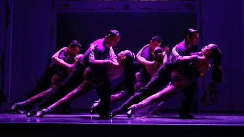 Couples performing a tango at the Café de los Angelitos Tango Show as the purple light shines on them in Buenos Aires