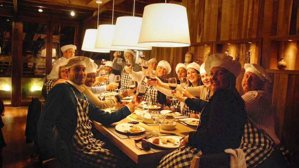 Group on a cooking experience smiling for the camera as they raise their wine glasses for a toast in Buenos Aires