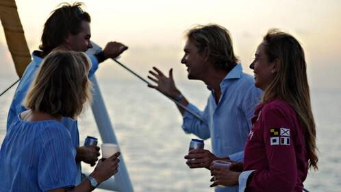 Couples enjoying drinks during sunset onboard the Tango catamaran
