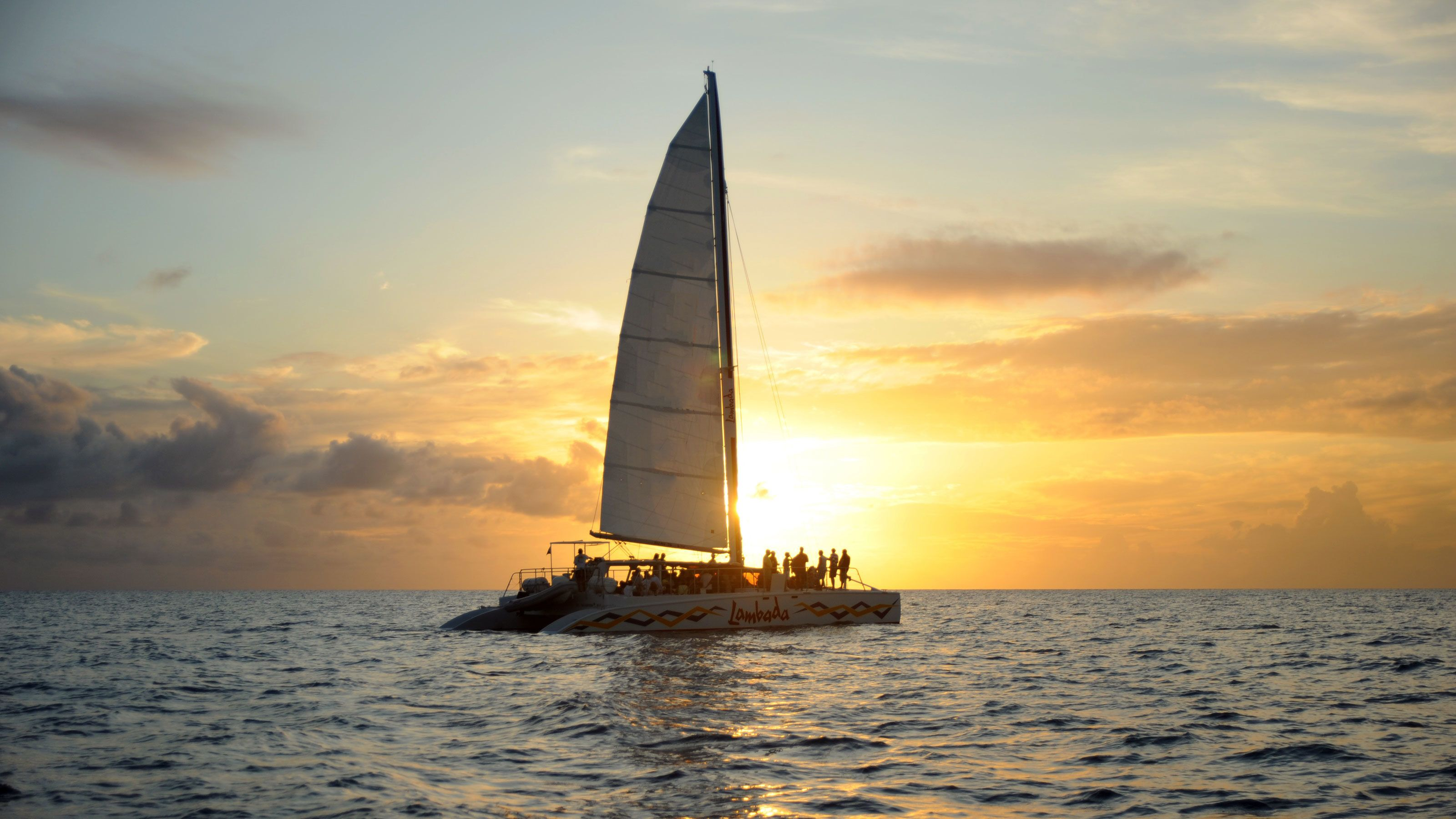 Lambada catamaran sailing through Simpson Bay during sunset
