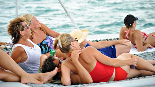 Couples sun bathing on the Lambada catamaran