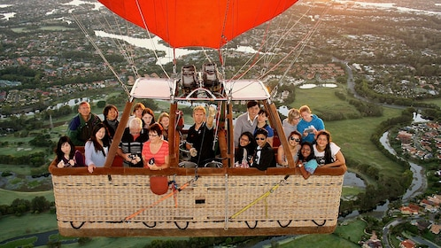 Large group of people in hot air balloon basket above the ground in Gold Coast