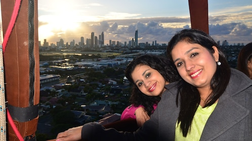 two women enjoy panorama view of city from hot air balloon in Gold Coast