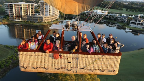 Large group of people excited to be in hot air balloon basket above the ground in Gold Coast