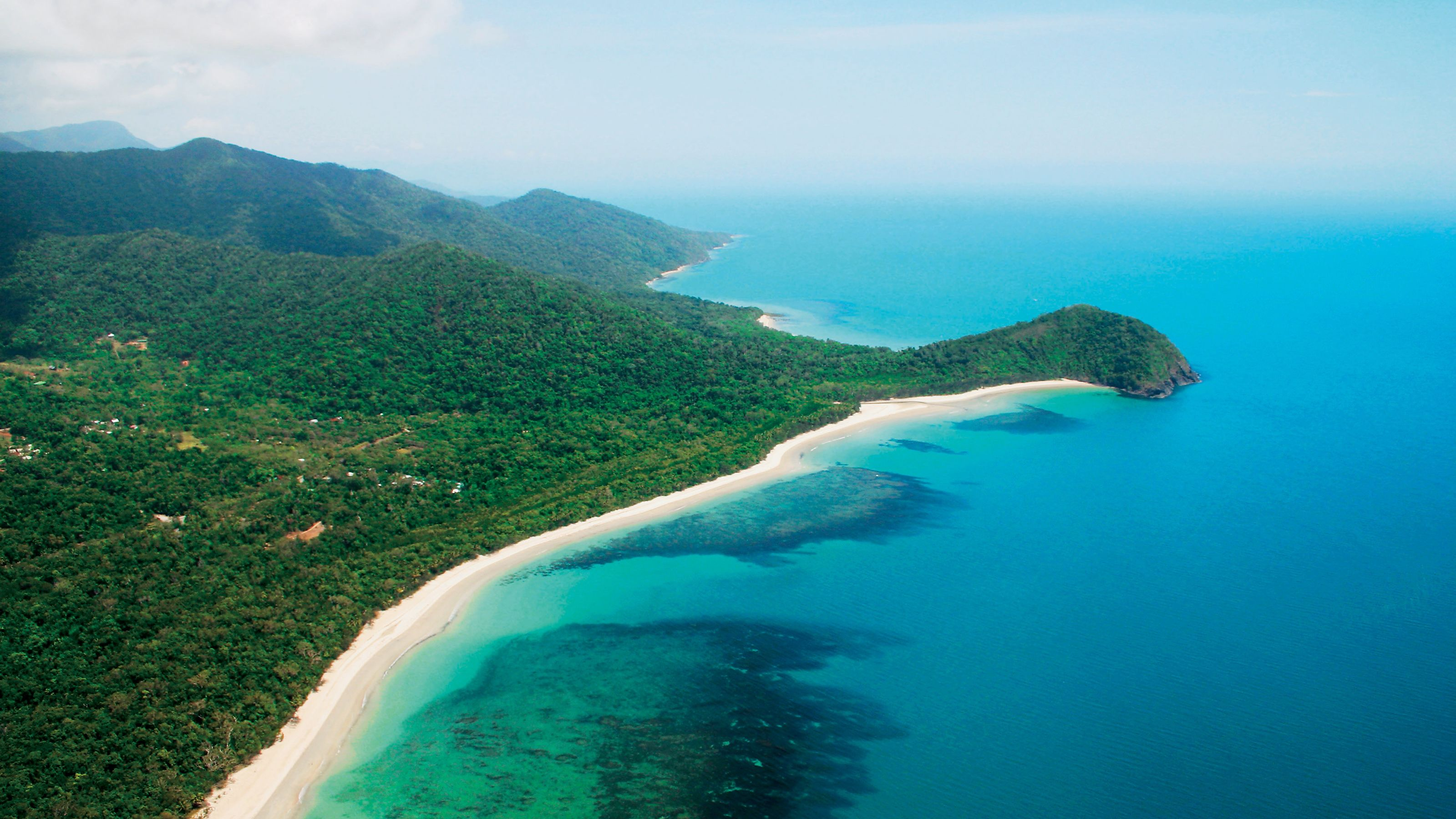 ariel veiw of green forest and sandy coast line of blue water.