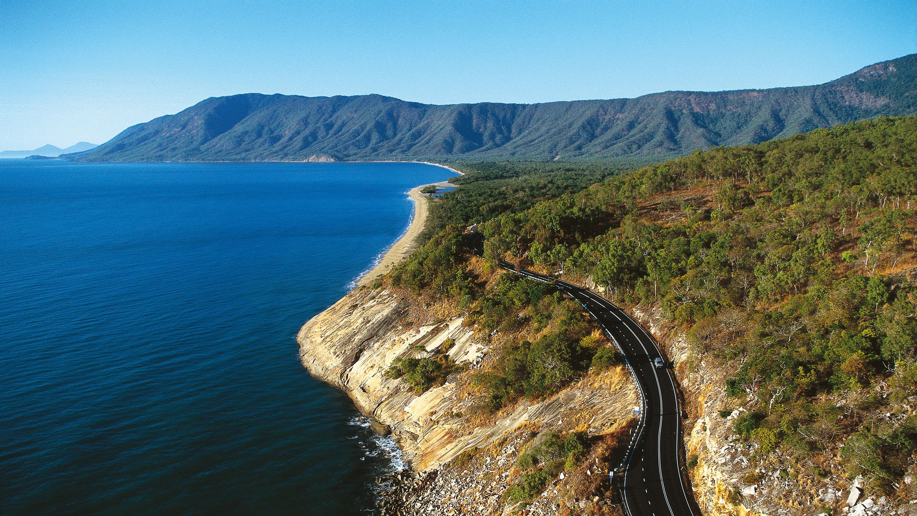 ariel view of a two lane highway hugging a rocky shoreline.