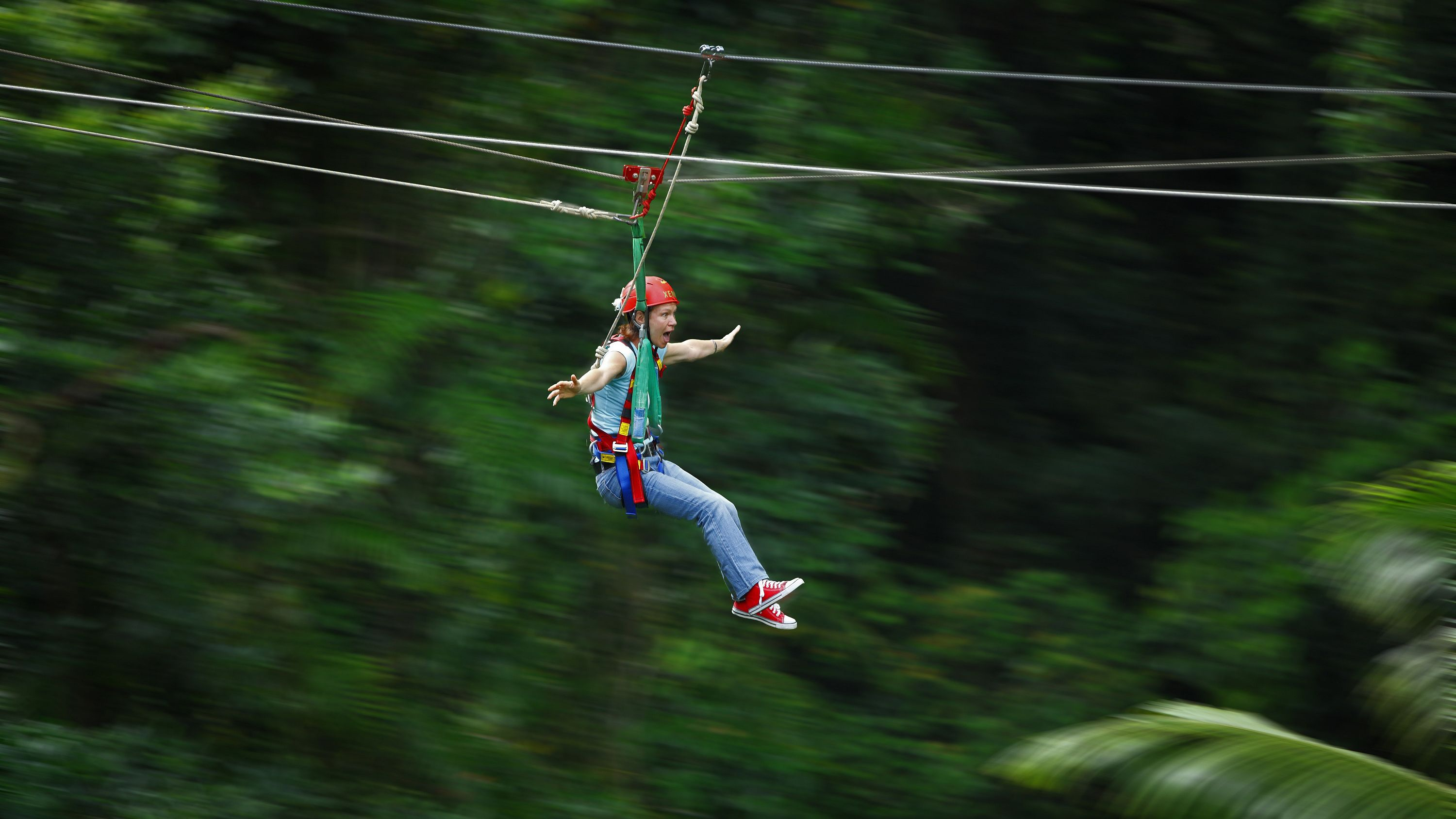 a happy girls quickly zip-lining down a zip among trees.