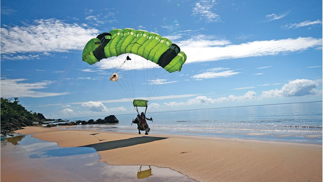 Skydivers parachuting down to beach on Tandem Skydive in Cairns Australia