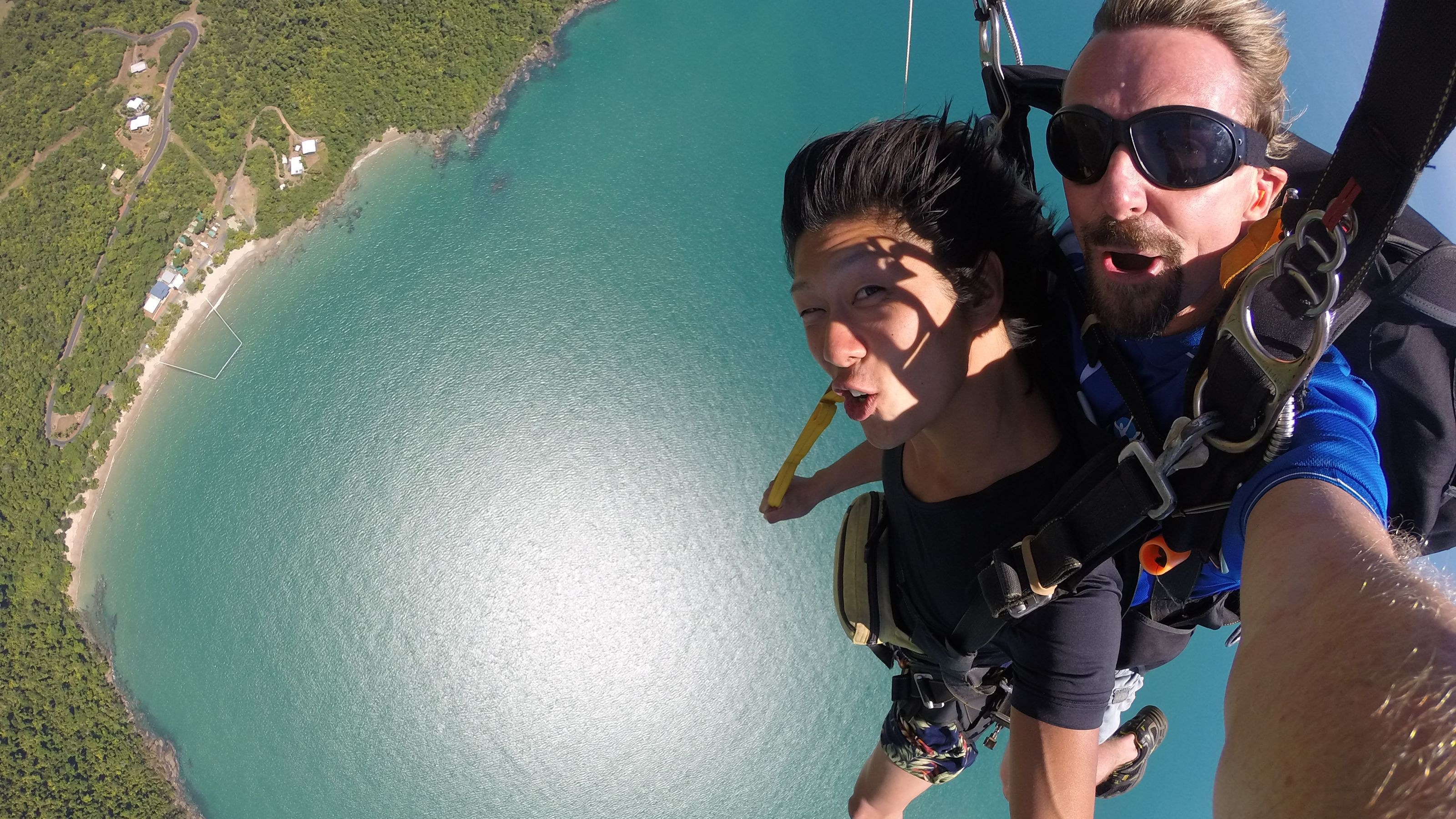 Girl fastened to professional Skydiver free falling in the Tandem Skydive in Cairns Australia