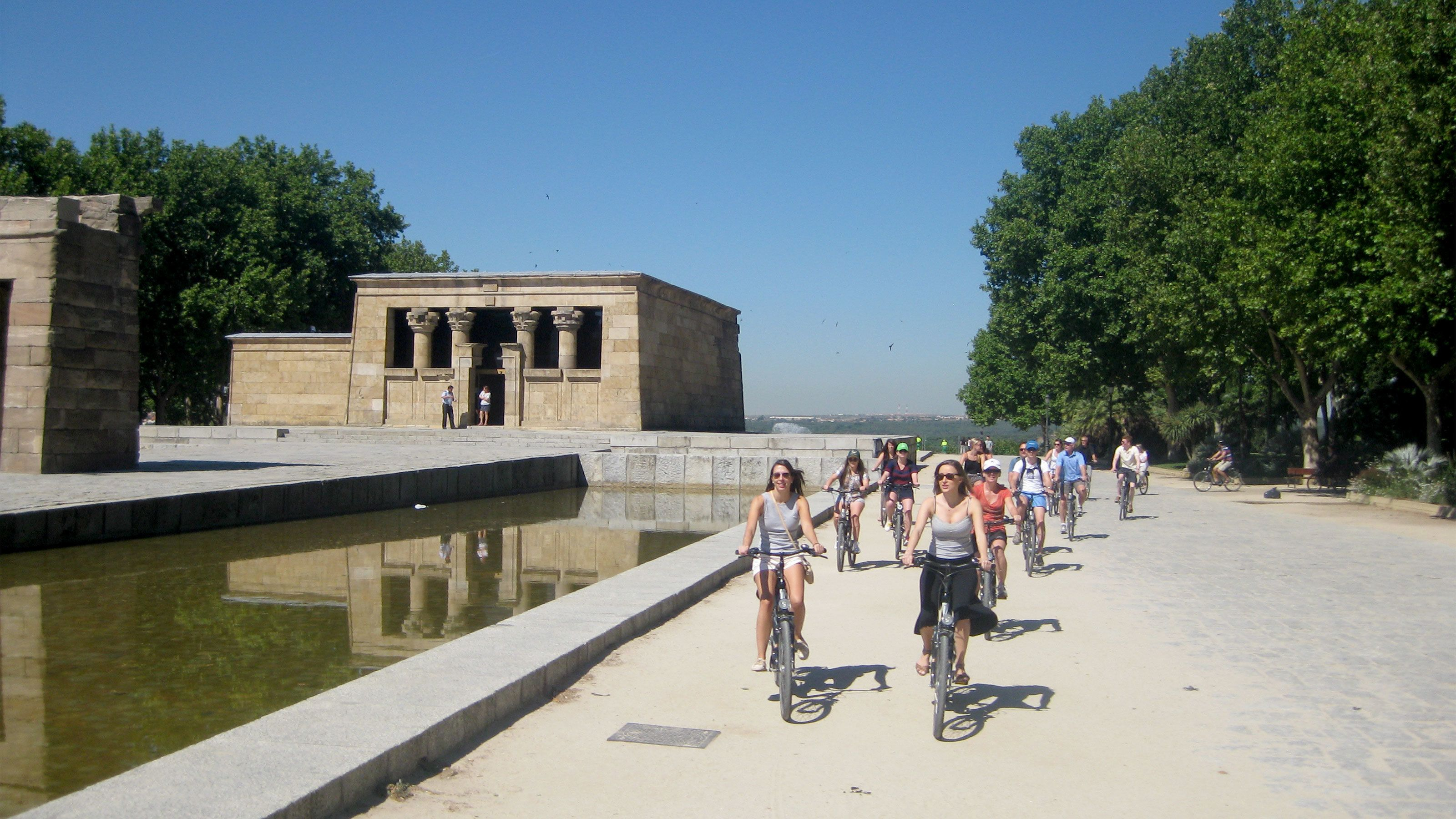 Group of bicyclists riding through the Temple of Debod which is an Egyptian temple in Madrid